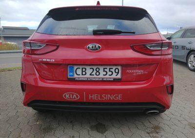 logo-mærke monteret på bagsiden af rød bil